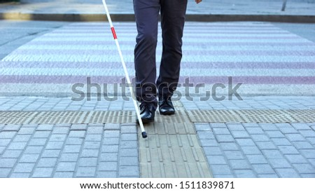 Visually impaired man using tactile tiles to navigate city, finishing crossroad