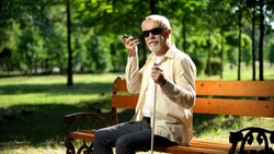 Visually impaired old man using voice control app in smartphone, innovations