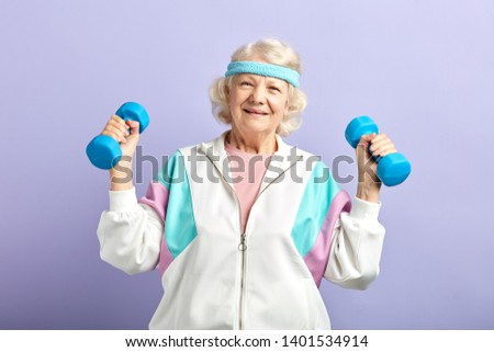 Vital senior grandma dressed in stylish sports suit exercising in the gym with dumbbells against violet wall.