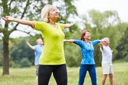 Vital seniors in a yoga or gym class with stretched arms