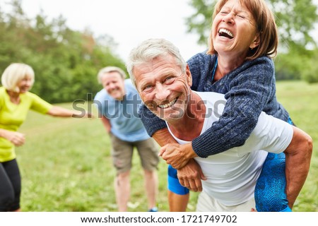 Vital seniors play together in the park in the summer and ride piggyback Foto d'archivio ©