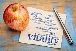 vitality and vital energy word cloud - handwriting on a napkin with a fresh apple