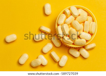 vitamin B tablets on yellow background #589727039