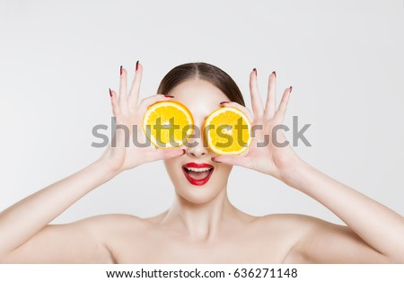 Vitamin C. A young woman holding two half oranges isolated white background #636271148