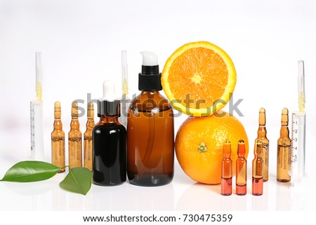 Vitamin C and Mesotherapy. Serum with vitamin C in ampoules, syringes and brown glass bottles, orange in a cut . Organic Natural Cosmetics Concept #730475359