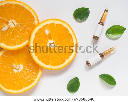 Vitamin C brown ampule for injection with fresh juicy orange fruit slices on white table. High dose vitamin c synthetic for white skin. Beauty product branding mock-up. Healthy lifestyle. Top view.