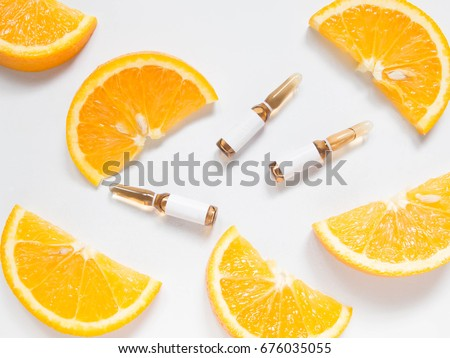 Vitamin C brown ampule for injection with fresh juicy orange fruit slides on white table. High dose vitamin c synthetic for white skin. Beauty product branding mock-up. Healthy lifestyle. Top view. #676035055