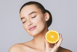 Vitamin C for skin. Delighted young pretty woman with closed eyes holding orange half over grey background