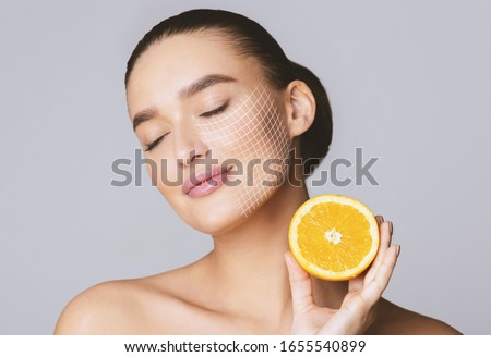Vitamin C for skin. Delighted young pretty woman with closed eyes holding orange half over grey background Photo stock ©