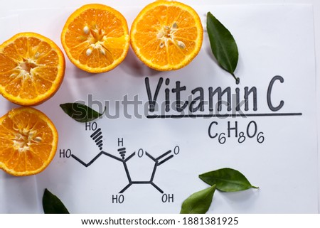 Vitamin C In Food Concept - Half Cut Oranges With Selective Focus And Vitamin C Structure And Chemical Formula. Zdjęcia stock ©