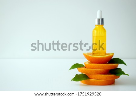 Vitamin C serum in cosmetic bottle on top of orange citrus slices with green leaves on white background. Citrus essential oil, cosmetics aromatherapy. Organic SPA cosmetics with herbal ingredients.