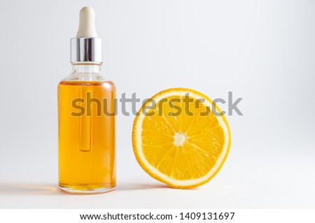 Vitamin C serum in cosmetic bottle with dropper and slice of orange on white background. Organic SPA cosmetics with herbal ingredients.