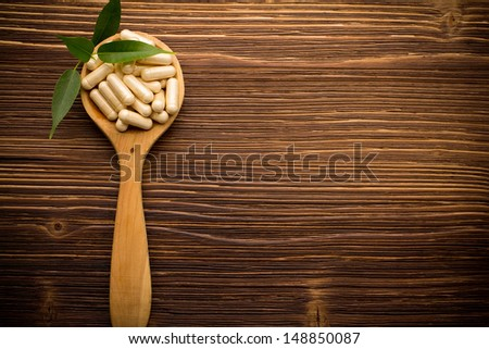 Vitamin capsules in a wooden spoon on a wooden background.