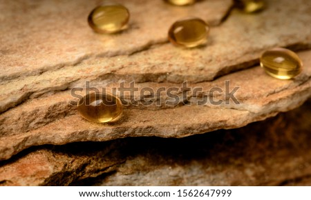 Vitamin capsules. Soft gel capsules on the surface of natural stone. Сlose up fish oil on gold background. Omega 3. Сoncept of health. Омега 3. gold pattern Сток-фото ©