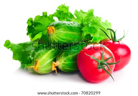 Vitamin collection of vegetables tomatoes and cucumbers with a branch and leaves of green salad on a white background