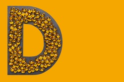 Vitamin D capsules laid out in the shape of the letter D on a orange background