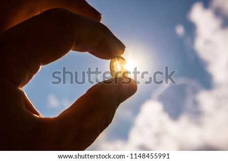 Vitamin D keeps you healthy while lack of sun. Fingers holding yellow soft shell D-vitamin capsule against sun and blue sky on sunny day. Cure concept.