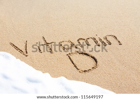 Vitamin D written in the sand with foam from a wave washing up - stock photo