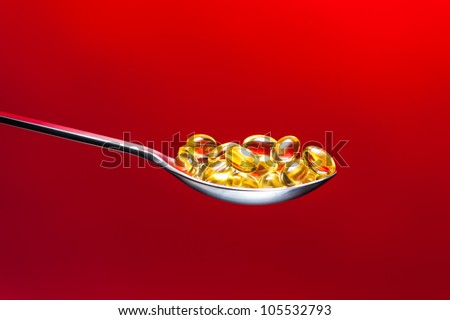 Vitamin E Capsules on a spoon in front of a red Background. Vitamin E Kapseln auf L�¶ffel vor Rot.