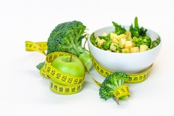 Vitamin-fitness diet, a plate of green salad, a green apple with a centimeter tape. Fresh Food and Roulette, Sports Diet, Raw Food Diet, Ketone Diet