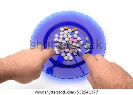 vitamin pills lying on a plate and eat them with a fork and a knife cut