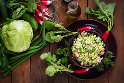 Vitamin salad of young vegetables: cabbage, radish, cucumber and fresh herbs. Top view