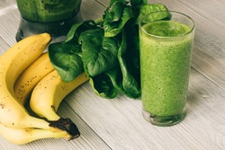 Vitamin Smoothies in a glass on a wooden table. On the table are also banana, spinach and a food processor.