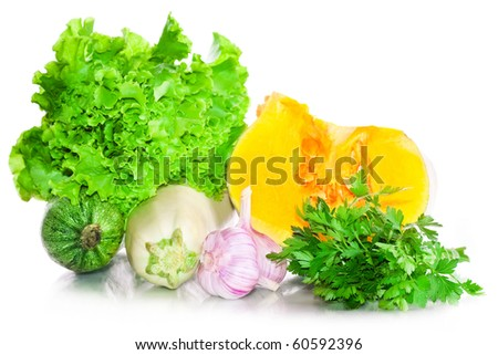 Vitamin vegetable collection: a pumpkin, a vegetable marrow, garlic, leaves of salad and parsley with reflection isolated on a white background