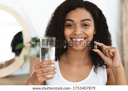 Photo of Vitamins And Food Supplements. Portrait Of Smiling Black Woman Holding Omega-3 Fish Oil Capsule And Water In Hands, Enjoying Healthy Lifestyle