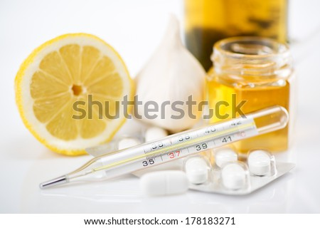 Vitamins and pills for treatment Cold And Flu. Lemon, tea, honey, garlic and Thermometer on white background. Selective focus. Focus on thermometer.