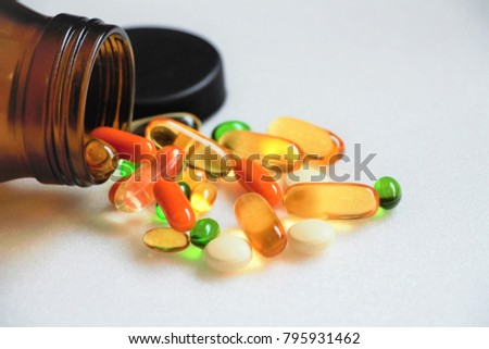 Vitamins and supplements on white background with a brown bottle. Vitamin c, vitamin E, vitamin D3, salmon oil, fish oil, co enzyme Q10.  #795931462