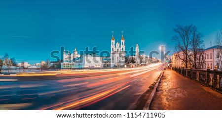 Vitebsk, Belarus. Panorama Of Evening Or Night View Of Famous Landmarks Is Assumption Cathedral, Church Of Resurrection Of Christ And Old Town Hall In Street Lights Illumination. Traffic Light Trails #1154711905