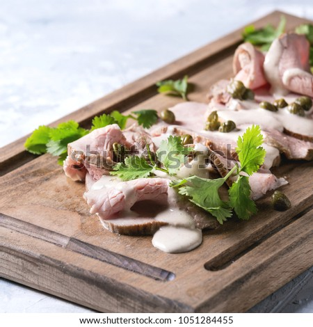 Vitello tonnato italian dish. Thin sliced veal with tuna sauce, capers and coriander served on wooden serving board over gray texture background. Square image #1051284455
