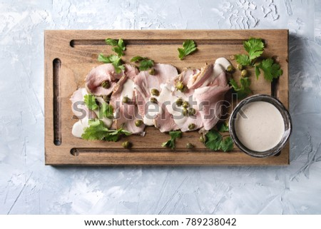 Vitello tonnato italian dish. Thin sliced veal with tuna sauce, capers and coriander served on wooden serving board over gray texture background. Top view, space #789238042
