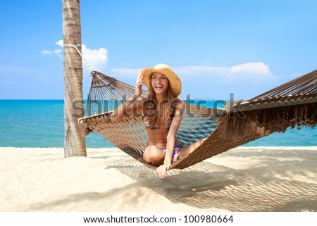 Vivacious beautiful woman wearing a straw sunhat relaxing in a hammock tied to a palm tree on a tropical island resort