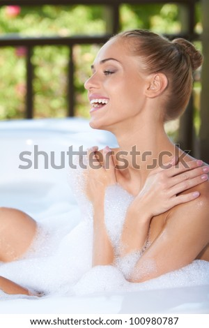 Vivacious blonde woman laughing in enjoyment as she soaks in the soapy bubbles of her bubble bath