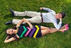 Vivacious teenage couple lying on their backs on lush green grass head to toe resting their arms on each others legs, overhead view of a stylish fashionable young man and woman