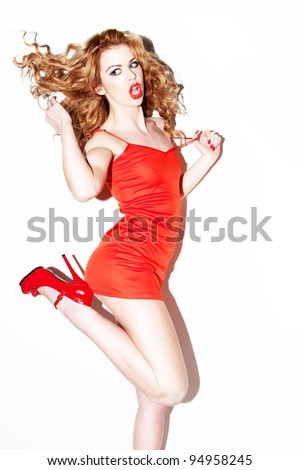 Vivacious young redhead woman dancing and kicking her heels in the air with her long wavy hair flying out behind.