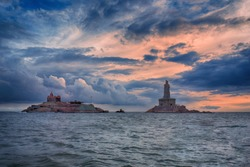 Vivekananda Rock memorial and the 133-feet tall stone statue of Thiruvalluvar at Kanyakumari, Tamil Nadu, India, in the Indian Ocean against the dark cloudy sky in the late evening. Incredible India.