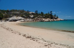 Vivid aqua waters and golden sands against rocky headland at Arcadia Bay Magnetic Island Queensland Australia