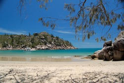 Vivid aqua waters and golden sands against rocky headland of Arcadia Bay Magnetic Island Queensland Australia