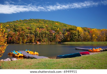 Vivid Autumn Lake Scene with Boats, Bright Sky and Colorful Trees