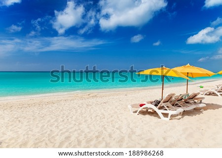 Vivid blues and turquoise with white sands, Grace Bay Beach, Turks & Caicos. Bright yellow beach umbrellas make a great contrast color
