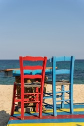 Vivid bright colrful wooden chairs - red and blue standing on the beach of blues sea in the background in Sarti , Greece.