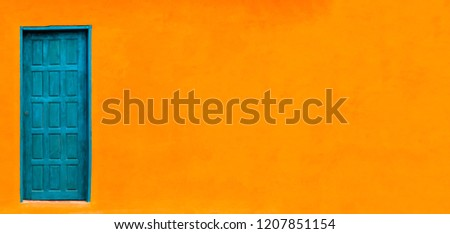 Vivid bright orange wall house facade with blue green closed door in left of large empty orange wide wall texture background space in panorama banner format with large copy space.