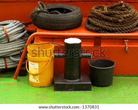 Vivid colored steel life consisting of buckets, ropes, and a tire on the deck of a ship