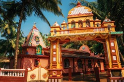 Vivid colorful Hindu Temple at Morjim amidst a coconut grove, North Goa, India.