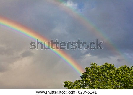Vivid double rainbow over the cloudy sky