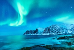 Vivid Northern lights during polar night on Lofoten Islands in Norway. Epic scene of dancing aurora borealis in the night sky over jagged mountain ridge and Arctic ocean on island Senja, polar circle.