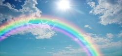 Vivid Rainbow Sky Website Banner  -  Wide blue sky with pretty clouds, a bright sun shining center top and a large rainbow arcing from left to right with copy space